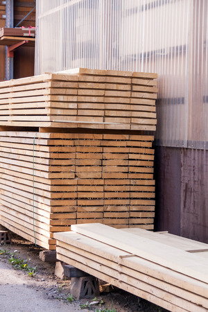 warehouse building: Wooden panels stored inside an industrial warehouse on metal shelving for use in construction and building, nobody in view Stock Photo