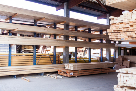 Wooden panels stored inside an industrial warehouse on metal shelving for use in construction and building, nobody in view photo