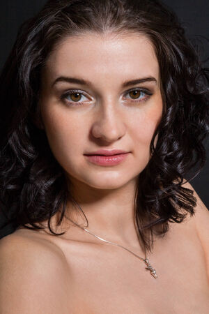 enigmatic: Ritratto scuro di una bella donna enigmatica con i capelli castani lunghi fino alle spalle ricci