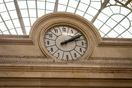 viewable: Circular clock inset into a stone building facade under a domed glass roof at a mall, station or terminal viewable by the public on their travels