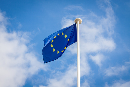 The fluttering flag of European Union on a pole, with a blue sky with white clouds in the background