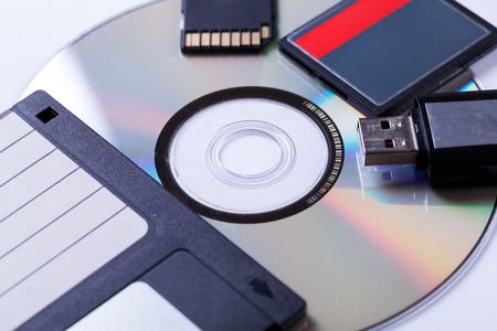 Selection of different computer storage devices for data and information including a CD-DVD, floppy disc, USB key, compact flash card and SD card viewed in a neat arrangement from overhead photo