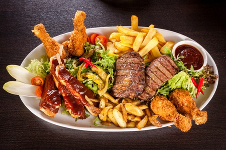 Wholesome platter of mixed meats including grilled steak, crispy crumbed chicken and beef on a bed of fresh leafy green mixed salad served with French fries and chutney or BBQ sauce in a dish