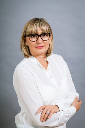 scholarly: Scholarly attractive middle-aged blond woman in glasses standing looking at the camera with folded arms against a grey background Stock Photo