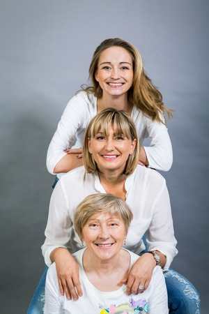 Three generations of attractive women with blond hair and a striking family resemblance posing together arm in arm looking at the camera with friendly smiles