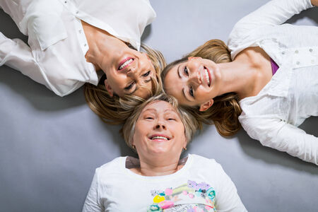 three generations of women: Three generations of attractive women with blond hair and a striking family resemblance posing together arm in arm looking at the camera with friendly smiles
