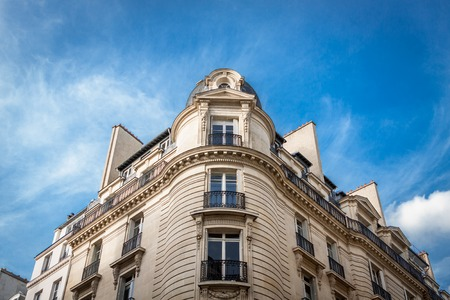 Exterior of a multi-storey historical townhouse in Paris with an ornate stone facade with tall windows and an architrave viewed low angle against a hazy blue sky Фото со стока