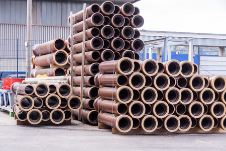 Plastic pipes stacked in a factory or warehouse yard for use in plumbing or sewage installations on a construction site Stock Photo