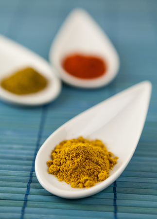 pungent: Dried ground spices in decorative pointed ceramic spoons for seasoning savory cooking with cayenne chili pepper, turmeric and curry powder for a pungent spicy taste
