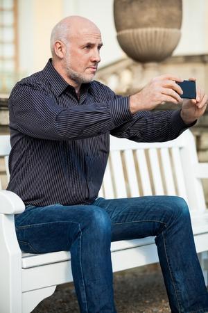 bald man: Atractivo hombre de mediana edad calvo sentado en un banco de madera en un entorno urbano de tomar una fotografía con su teléfono móvil Foto de archivo