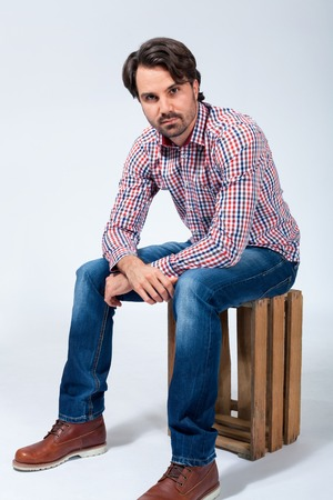 charismatic: Handsome trendy young man sitting on a wooden box looking at the camera with a charming friendly smile on a blue-grey studio background Stock Photo
