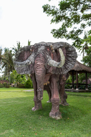naturalistic: Realistic naturalistic elephant statue standing on a lawn at a park or landscaped garden in Bali