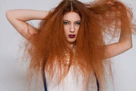 tousled: Female model with red lipstick playing with frizzy hair on white background