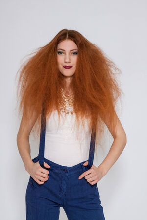frizzy hair: Female model with red lipstick playing with frizzy hair on white background