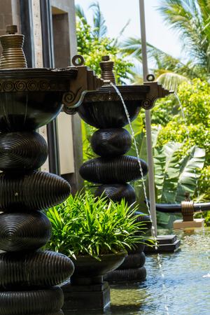 water feature: Ornamental fountain in a shallow pond in a landscaped garden outside a building or house in Bali with jets of water cascading into the pool below and lush green potted plants