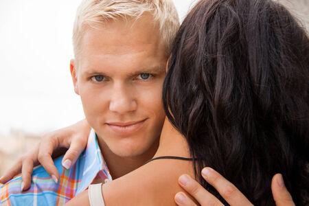 Romántica joven rubio guapo, abrazando a su novia mirando más allá de la parte de la cabeza a la cámara con una sonrisa Foto de archivo - 29500374