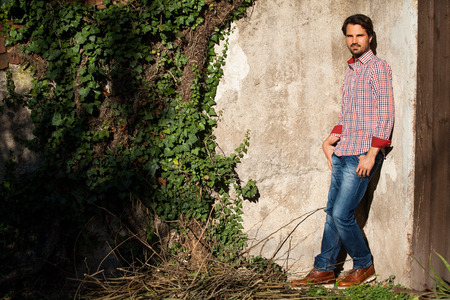 nonchalant: Male model relaxing leaning against wall with hands in pocket
