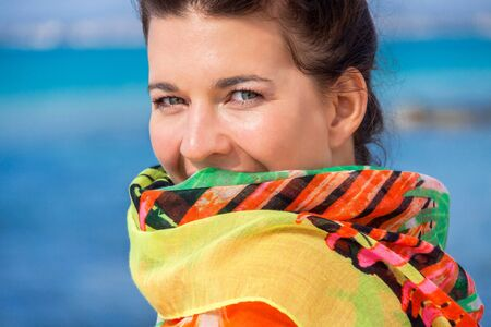 vivacious: Beautiful vivacious young woman wearing a bikini and holding a colorful scarf around her shoulders  Stock Photo