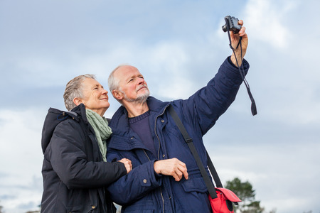 Elderly couple taking a self portrait on a compact digital\ camera posing in the open air and sunshine with their heads close\ together smiling at the lens