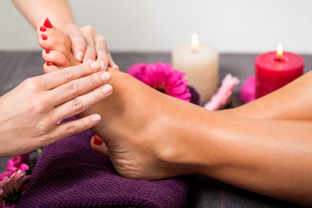 reflexologie: Femme ayant un traitement de p�dicure dans un spa ou un salon de beaut� avec la p�dicure masser la plante des pieds avec une pierre ponce pour nettoyer les peaux mortes et stimuler le tissu