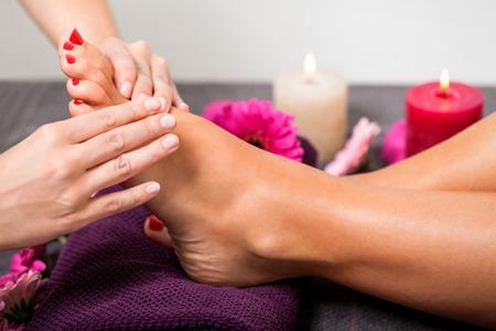 Mujer que tiene un tratamiento de pedicura en un salón de spa o de belleza con la pedicura masajear las plantas de los pies con una piedra pómez para limpiar la piel muerta y estimular el tejido