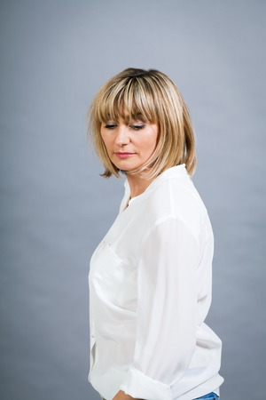 Smiling confident middle-aged blond woman in a fresh white blouse standing with her hand on her hip smiling at the camera, on grey photo