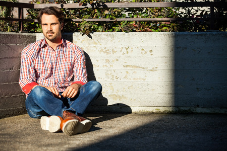 suave: Male model relaxing leaning against wall with hands in pocket