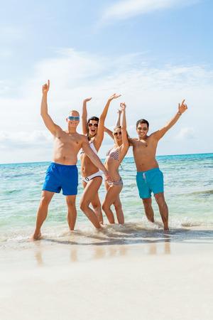 young happy friends havin fun on the beach summer holiday Фото со стока