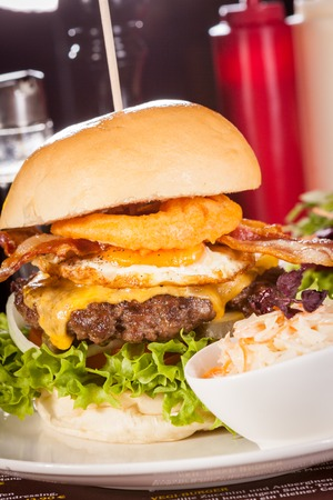 Delicious egg and bacon cheeseburger with a nutritional filling of salad ingredients, a ground beef patty, cheese, fried egg and crispy bacon on a white crusty roll photo