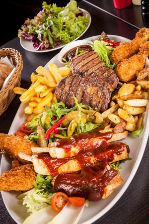 Wholesome platter of mixed meats including grilled steak, crispy crumbed chicken and beef on a bed of fresh leafy green mixed salad served with French fries and chutney or BBQ sauce in a dish photo