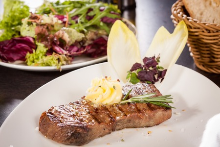 potherb: Tasty grilled beef steak topped with a twirled knob of butter and a sprig of fresh rosemary and served on a white plate, close up view