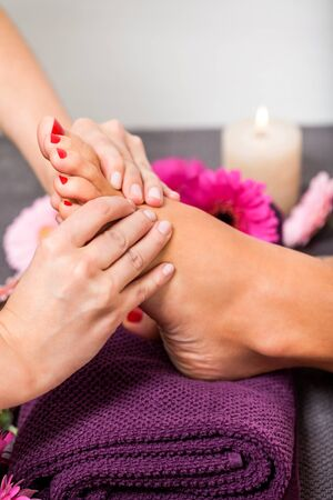 Woman having a pedicure treatment at a spa or beauty salon with the pedicurist massaging the soles of her feet with a pumice stone to cleanse dead skin and stimulate the tissue photo