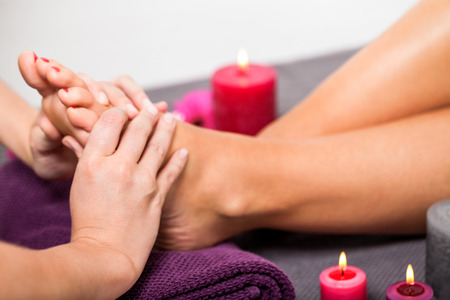 stimulate: Woman having a pedicure treatment at a spa or beauty salon with the pedicurist massaging the soles of her feet with a pumice stone to cleanse dead skin and stimulate the tissue