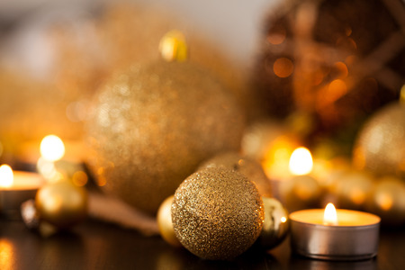 stock photo warm gold and red christmas candlelight background with burning tea lights amongst random gold and red baubles in a warm glowing light with