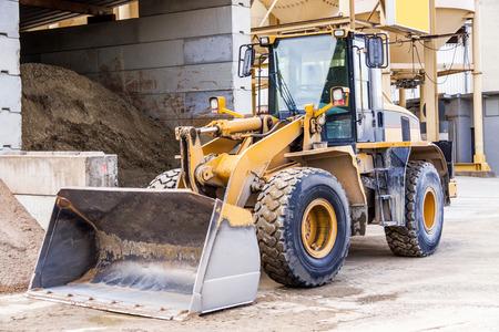front loader: Parked pay loader near pile of dirt