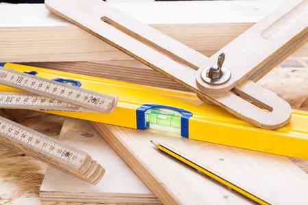 joinery: Primo piano vista di un colorato livello falegnami gialle, righello e ad angolo retto disteso su tavole di legno duro nuovo insieme con una matita per le misurazioni in un concetto di carpenteria, edilizia, bricolage e falegnameria