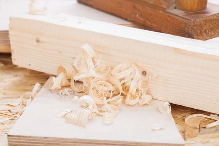 joinery: Primo piano vista di un piano di legno portatile di legno utilizzati per lisciare e livellare la superficie di una tavola di legno circondata da trucioli di legno fresco in un fai da te, falegnameria, carpenteria o concetto falegnameria Archivio Fotografico