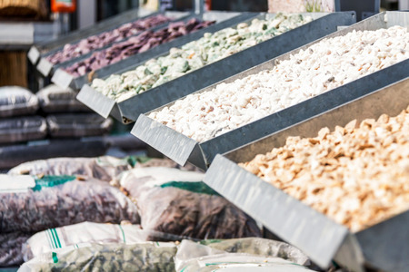 Stock at a nursery or landscaping business with weathered smooth stones in assorted shapes and sizes in metal bins with stacked sacks of potting soil and fertiliser
