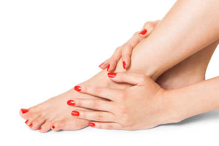 pedicure: Woman with beautiful neatly manicured red finger and toenails sitting with bare feet clasping her ankles to display her nails, closeup on white in a fashion and beauty concept