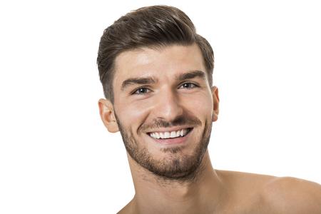 화이트 절연 관능적 인 섹시 포즈에서 그의 턱을 그의 손으로 카메라를 골똘보고 서 잘 생긴 벗은 수염 난 젊은이