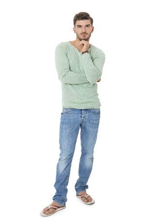nonchalant: Handsome confident relaxed handsome young man with a beard posing with his hands in his pockets in jeans and slip slops, isolated on white