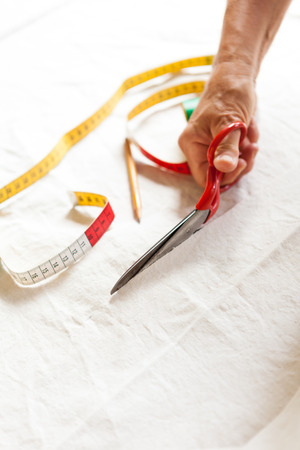 Hand Cutting Cloth with Scissors with Measuring Tape and Pencil Nearby photo