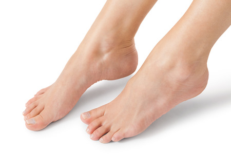 Woman with neat manicured natural nails without nail varnish showing her hands and bare feet in a beauty concept on a white