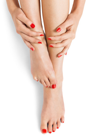neatly: Woman with beautiful neatly manicured red finger and toenails sitting with bare feet clasping her ankles to display her nails, closeup on white in a fashion and beauty concept