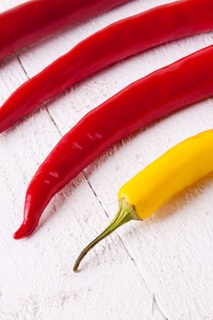 pungent: Fresh red and yellow chili peppers with a small bowl of dried cayenne pepper spice for use as a pungent hot seasoning and flavoring in cooking Stock Photo