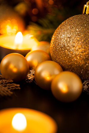 stock photo warm gold and red christmas candlelight with burning tea lights amongst random gold and red baubles in a warm glowing light with copyspace