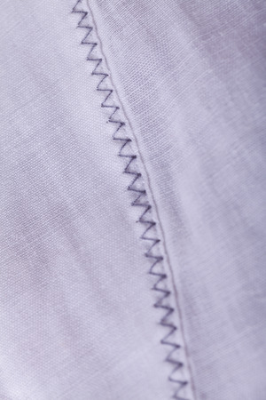 hem: Closeup Shoot of Small Buttons on White Flax Cloth.