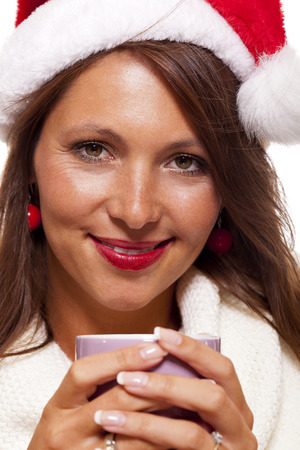 Cold attractive young woman with a cute smile in a festive red Santa hat sipping a hot mug of coffee that she is cradling in her hands to warm up in the winter weather, on white photo