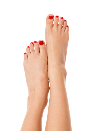 bare foot: Sexy slender female feet with carefully pedicured fashionable red nails displayed in the crossed position on white with copyspace Stock Photo