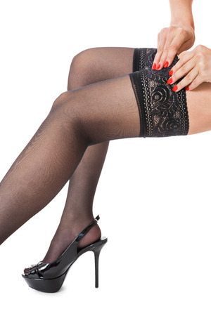 hold ups: Sensual portrait of slender sexy female legs in elegant stilettos and black stockings with lacy tops in profile isolated on white